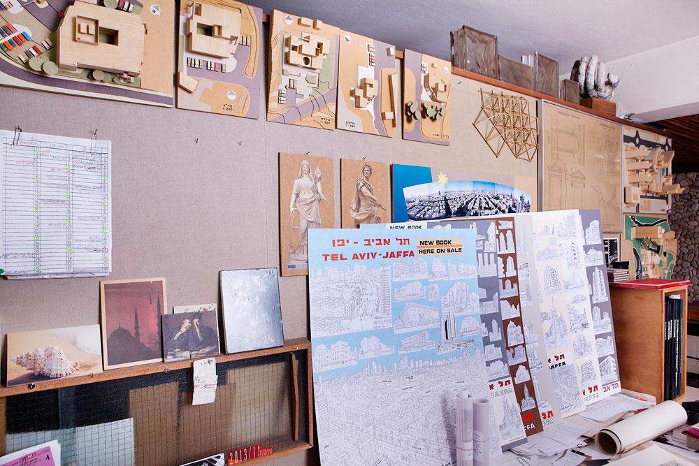 """קיר במשרד: מודלים של מרפאות במחנות צה""""ל, תוכניות של מבנים ורישומים מתוך הספר החדש. משולם ממשיך להגיע למשרד מדי יום, מגוהץ ומחויט, למרות שאין בו פעילות (צילום: ענבל מרמרי)"""