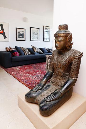 בובת בודהה גדולה וכלי מוזיקה מאפריקה בסלון (צילום: ענבל מרמרי)