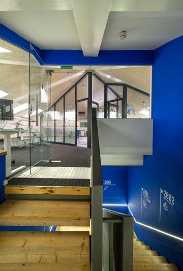 חדר המדרגות נצבע בכחול, עם ציר זמן שמסמן אבני דרך של החברה (צילום: אילן נחום)