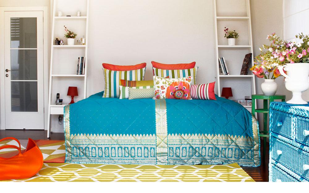 גם חדר השינה רוהט במיטה ובסולמות צד שהובאו מהדירה הקודמת. את ההבדל עושים פריטי הטקסטיל: כיסוי מיטה וכריות בסגנון מרוקאי, שטיחים גיאומטריים ושידת נצרים שנצבעה טורקיז (צילום: אפרת לוזנוב)