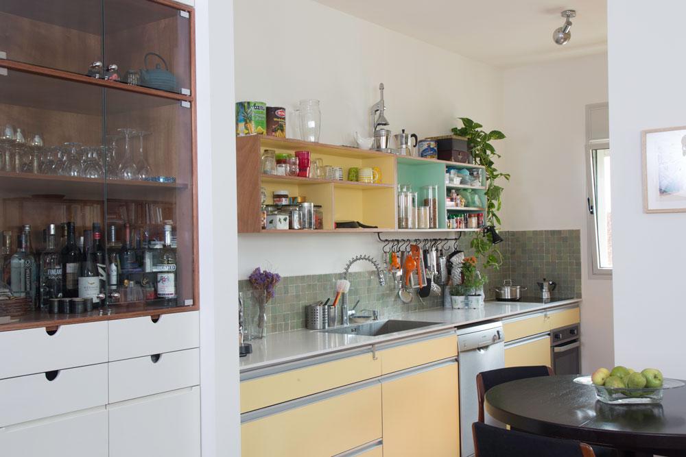 הקיר הלבן חופה בקרמיקה ירקרקה. משמאל חלק מהארון שנבנה בין המטבח למבואת הכניסה (צילום: יהונתן ה. משעל, סטיילינג צילומים: סברינה צגלה)