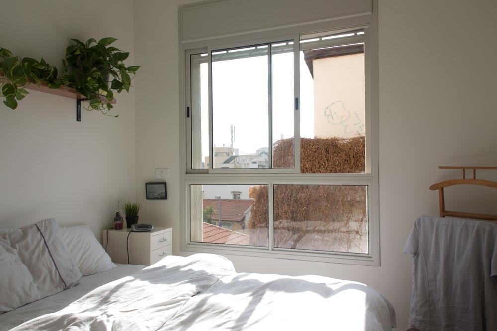 חלון חדר השינה פונה אל נוף השכונה, שמתאפיינת בבתים ישנים ונמוכים יחסית. הדיירים הוסיפו תריסים חשמליים, שלא נכללו בסטנדרט הקבלני  (צילום: יהונתן ה. משעל, סטיילינג צילומים: סברינה צגלה)