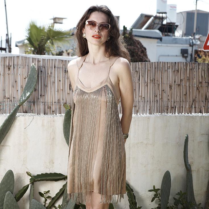 """אניה פליט בחצר ביתה, לבושה בשמלה שעיצב ויוי בלאיש. """"צורת העבודה שלו מרגשת"""" ( צילום: ניקיטה פבלוב )"""