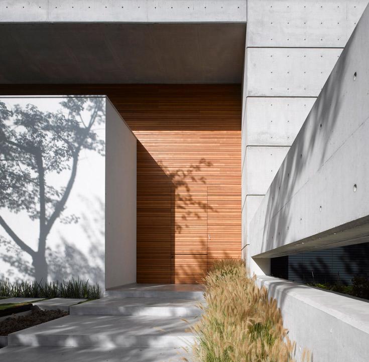 דלת הכניסה מובלעת במשטח בצורת ר', שעשוי סרגלי עץ טיק. אלמנט העץ חוצה את מעטפת הבטון המסיבית (צילום: עמית גרון )