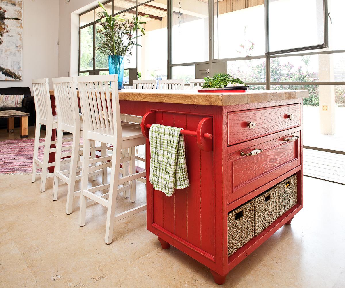 האי במטבח משמש לאכילה, עבודה ואחסון. הוא עשוי פלטת עץ אלון שכמעט לא עובדה, ארון ורגליים מגולפות שנצבעו אדום עז (צילום: טל ניסים)