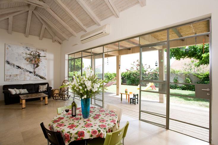 תקרה גבוהה ומשופעת חופתה עץ לבן. דלת הזכוכית נמתחה על תשעה מטרים ומוסגרה בברזל בלגי באפור-ירוק (צילום: רני לוריא)