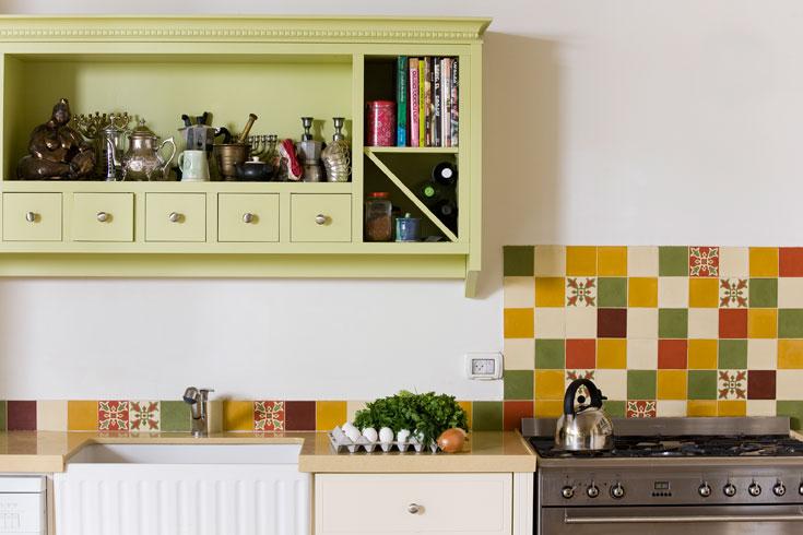 קיר המטבח מחופה אריחי בטון קטנים ומצויירים. גם אם נדמה שהונחו בצורה אקראית, אביטל תכננה את השיבוץ בקפידה (צילום: רני לוריא)