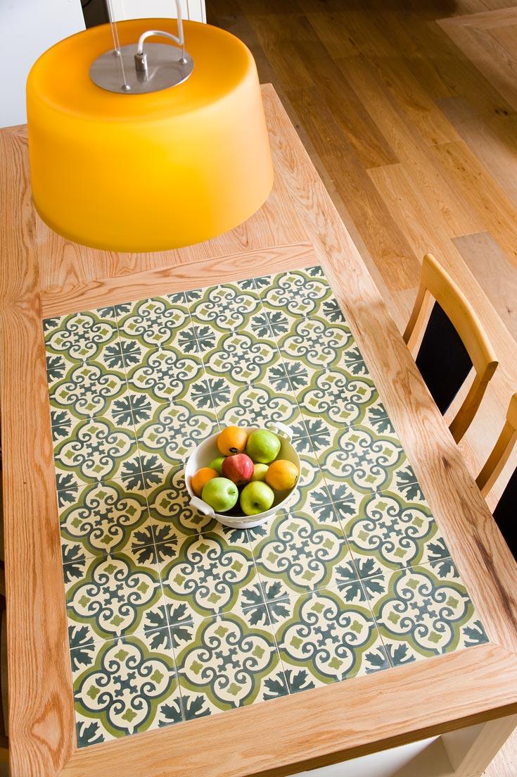 """השולחן במטבח משמש גם לבישול וגם לאכילה, ולצידו כסאות בר מעץ וקש מ""""פיק אפ"""" בגעש. האהיל עשוי מזכוכית צהובה, ונקנה בעיר טירה הסמוכה. השולחן מצופה באריחים ירקרקים היוצרים צורת שטיח הומוגני (צילום: רני לוריא)"""