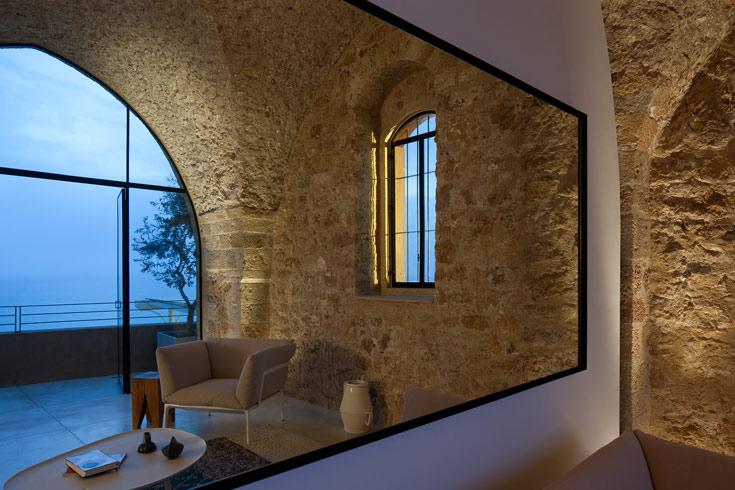 תאורת רצפה הזורקת אור אל קמרונות האבן הגבוהים, מדגישה את אבן הכורכר המקומית (צילום: עמית גרון)