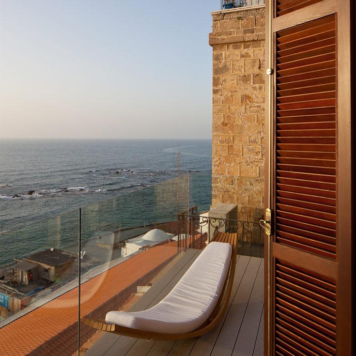 מערבה מכאן. המרפסת הפונה אל הים, מבעד למעקה שקוף (צילום: עמית גרון)