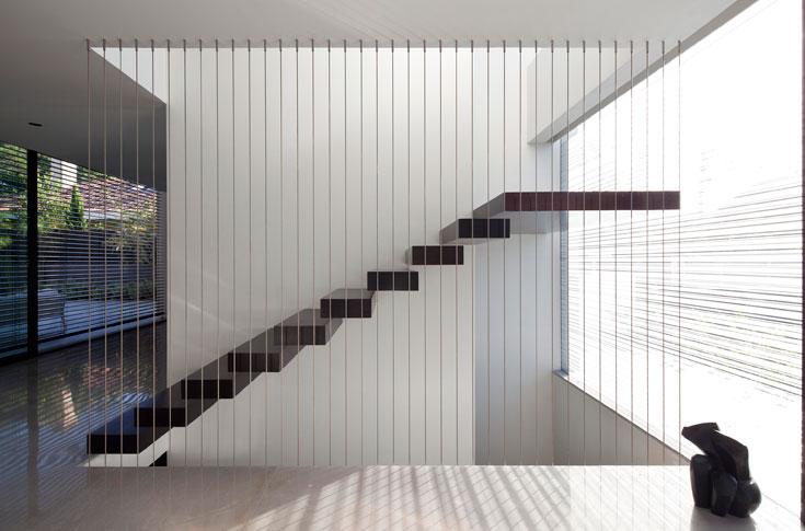 המדרגות – מהמרתף עד לקומה העליונה – עטופות עץ ותלויות על הקיר באמצעות קורת ברזל סמויה. המעקה עשוי כבלי נירוסטה (צילום עמית גרון)