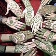 נשים פקיסטניות מקשטות את ידיהן בעיטורי חינה לכבוד עיד אל פיטר