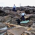 שוטרים ממשטרת ההגירה עומדים על ערימת משטחי עץ בחצר ששימשה מסתור לעובדים זרים מתאילנד