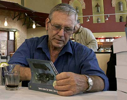 Amos Oz signs his book, 2005 (Photo: Shaul Golan)