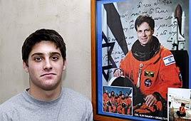 אסף רמון לצד תמונת אביו. צילום: AFP