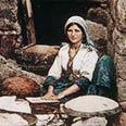 אשה אופה לחם. צילום מסוף המאה ה- 19.