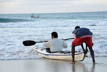 אחד הדייגים משלח את יובל לים. הגלים לפעמים מחזירים את הקיאק לחוף (צילום: מישה הויכמן, טבע הדברים) (צילום: מישה הויכמן, טבע הדברים)