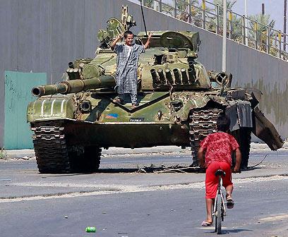 ילד על טנק שהיה שייך לכוחות קדאפי, ליד טריפולי  (צילום: רויטרס) (צילום: רויטרס)