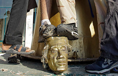 Rebels stomping on Gaddafi statue (Photo: AP)
