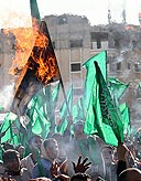 Hamas supporters torch Israeli flags (Photo: AP)
