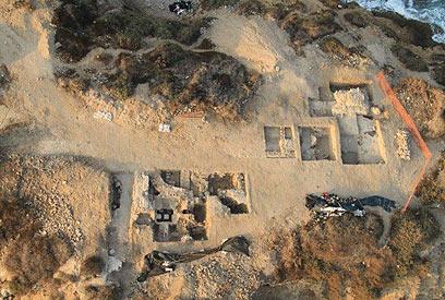 יבנה-ים: מבט-על של שטחי החפירה שעל משטח השונית. מימין נראים מגדל וחומות המשולבות אתו, ואילו משמאל, שרידי בית המרחץ עם עמודי חדר החמים (צילום: סקייויו)