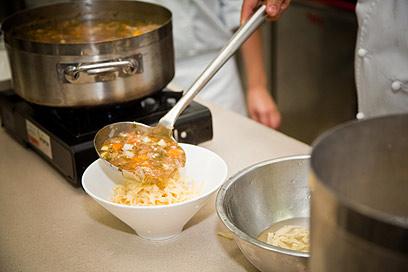 את המרק מוזגים על האיטריות, לא להפך. לגמאן בתהליך ההכנה (צילום: תום להט)