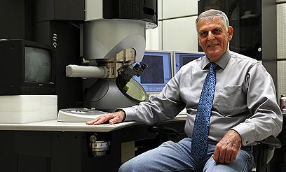 """שכטמן ליד המיקרוסקופ האלקטרוני. """"פעם הגבישים היו קטנים"""" (צילום: אבישג שאר-ישוב)"""