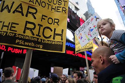 דור העתיד נגד חמדנות התאגידים. אב ובתו מפגינים בטיימס סקוור (צילום: AFP) (צילום: AFP)