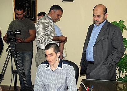 אבו מרזוק מאחורי שליט. אולץ להתראיין (צילום: AP) (צילום: AP)