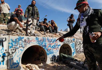 לוחמים מצביעים על פתח תעלת ביוב שבה לטענתם הסתתר קדאפי (צילום: רויטרס) (צילום: רויטרס)