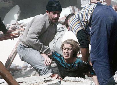 מחלצים אישה שנקברה תחת ההריסות ברעש האדמה (צילום: AP) (צילום: AP)