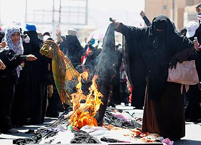 """נשים שורפות את כיסויי הגוף ברחוב. """"מי מגן ל נשות תימן החופשיות?"""" (צילום: רויטרס) (צילום: רויטרס)"""