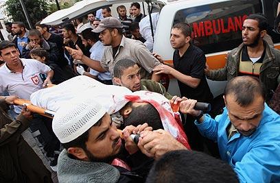 הפלסטינים שנפגעו מפונים מזירת התקיפה (צילום: AFP) (צילום: AFP)