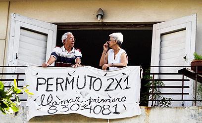 שלט להחלפת דירה ניתלה מחלון בהוואנה, בירת קובה (צילום: AP)