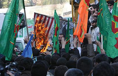 שורפים דגלים, היום בהפגנה באראן (צילום: AP)