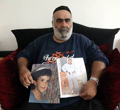 """יוסף סלהוב עם תמונות בנו. """"היה עוד דבר כזה במדינת ישראל?"""" (צילום: מוטי קמחי) (צילום: מוטי קמחי)"""
