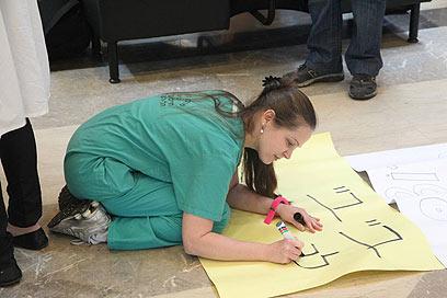 מכינים את השלטים. בהפגנה בשיבא (צילום: מוטי קמחי) (צילום: מוטי קמחי)