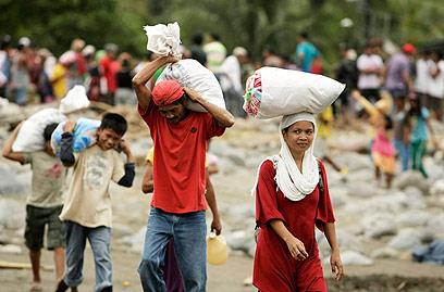 מעבירים שקי מזון בפיליפינים אחרי האסון (צילום: AP) (צילום: AP)