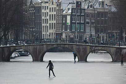 באמסטרדם יצאו תושבים להחליק על תעלה שקפאה (צילום: AP) (צילום: AP)