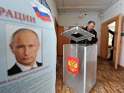 20 שנה בלי אלטרנטיבה ראויה. קלפי בעיר אולשה וכרזת בחירות של פוטין (צילום: AFP) (צילום: AFP)