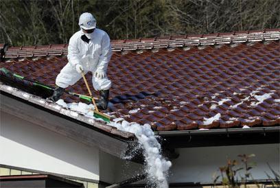 פועל מקרצף גג של בית במחוז פוקושימה (צילום: EPA) (צילום: EPA)