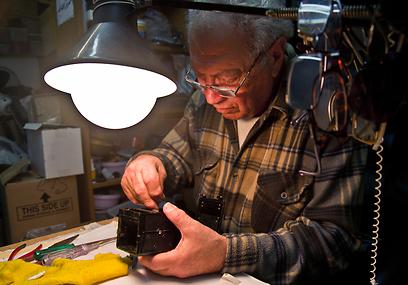 """יענקל'ה מ""""פוטו דורון"""" מתקן את המצלמה (צילום: יניב ברמן) (צילום: יניב ברמן)"""