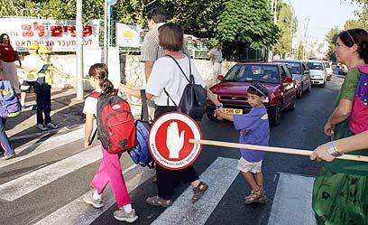 """הורים וילדים בדרך לביה""""ס. """"אוטובוס מהלך"""" (צילום: עמית שאבי)"""