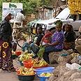 רוכלת מוכרת בננות ברחוב הראשי של עיירה קטנה בטנזניה