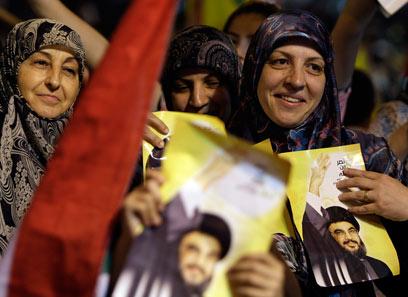 תומכות חיזבאללה אוחזות בתמונות נסראללה בעת נאומו (צילום: AP) (צילום: AP)