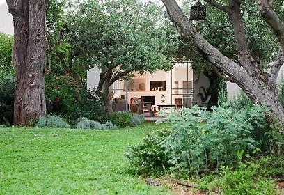 שביל הגישה לבית באווירה נוסטלגית. משמאל חלקו הישן של הבית, עם גג הרעפים ותריסי העץ בחלונות חדרי השינה (צילום: שי אפשטיין) (צילום: שי אפשטיין)