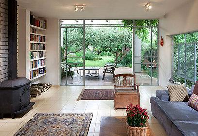 בסלון ספרייה מעץ צבוע שלייפלק, שטיחי קילים וקיר לבנים. קמין העצים היה בבית ורק מוקם מחדש (צילום: שי אפשטיין) (צילום: שי אפשטיין)