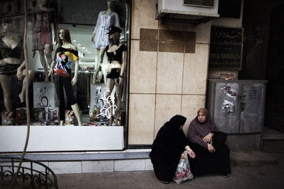 נשים מצריות בלבוש מסורתי ליד חנות בגדים (צילום: AFP) (צילום: AFP)