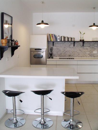 שילוב בין המטבח הלבן והמודרני לבין האביזרים השחורים והכפריים ליצירת המשכיות בין הסלון למטבח ()