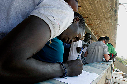 """אזרח דרום סודן חותם על """"עזיבה מרצון"""" (צילום: אליעד לוי) (צילום: אליעד לוי)"""